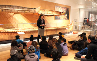 Royal Ontario Museum's Hack the ROM program. Indigenous student group with presenter in front of birchbark canoes