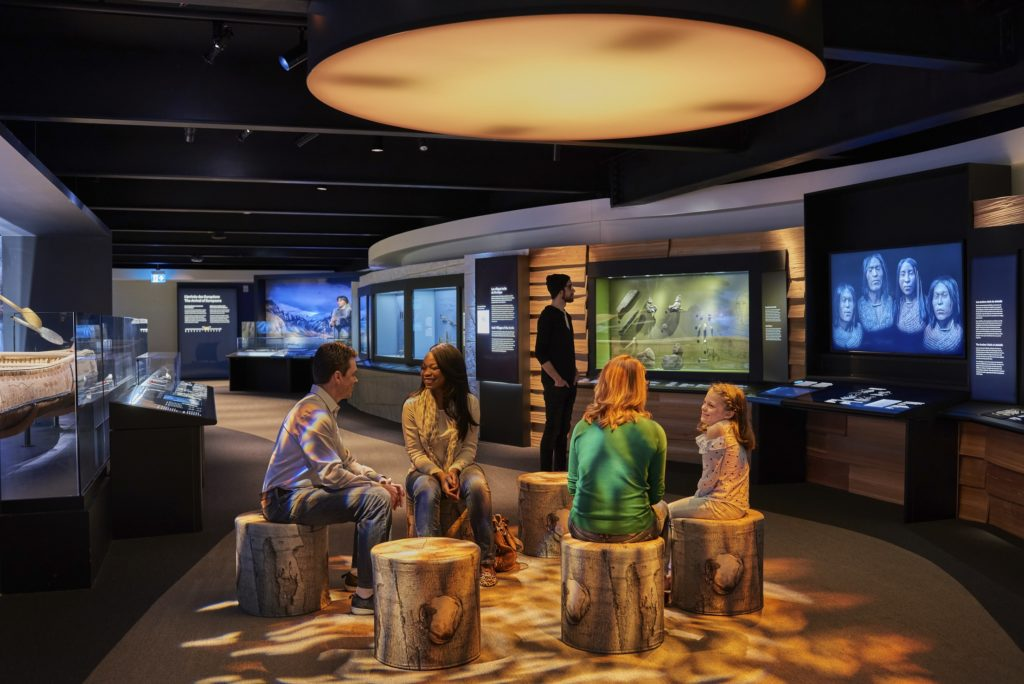 Shishalh Nation exhibition module in the Canadian History Hall. Four people are seated on imitation stumps in the gallery space with digital interactives around them.